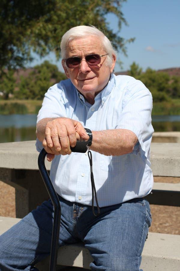 Vieil homme avec la canne au stationnement photo libre de droits