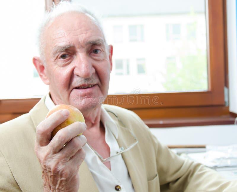 Vieil homme avec la pomme image stock