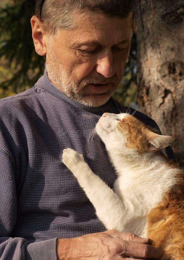 Vieil homme avec un chat images stock