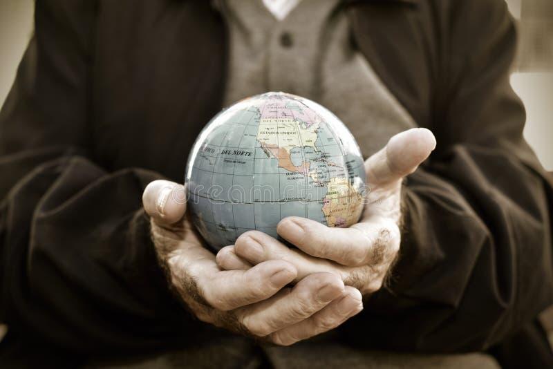 Vieil homme avec un globe du monde dans des ses mains image libre de droits
