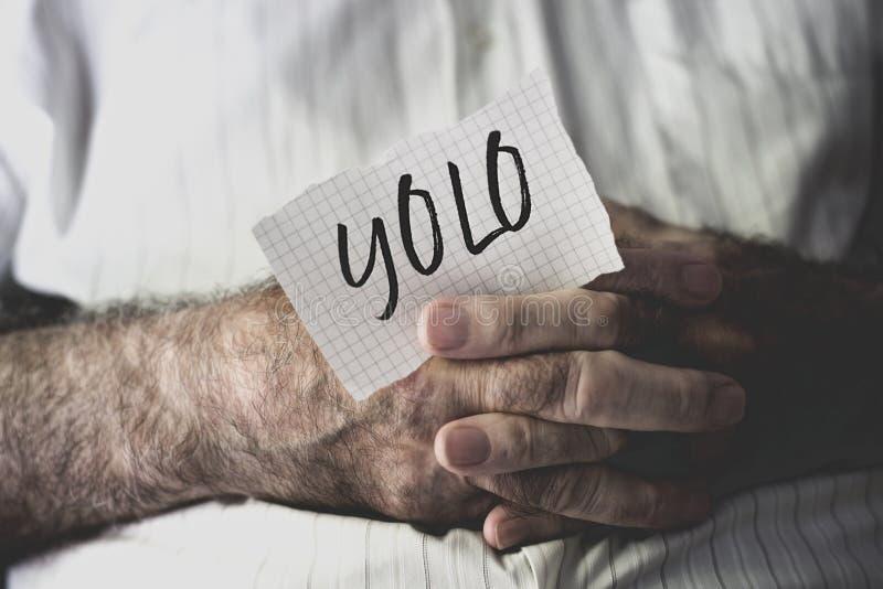 Vieil homme avec une note avec le mot yolo image libre de droits