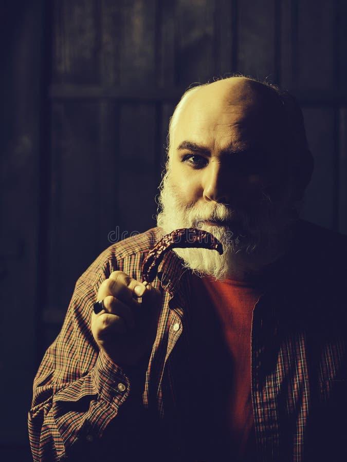 Vieil homme barbu avec le poivre de piments photo stock