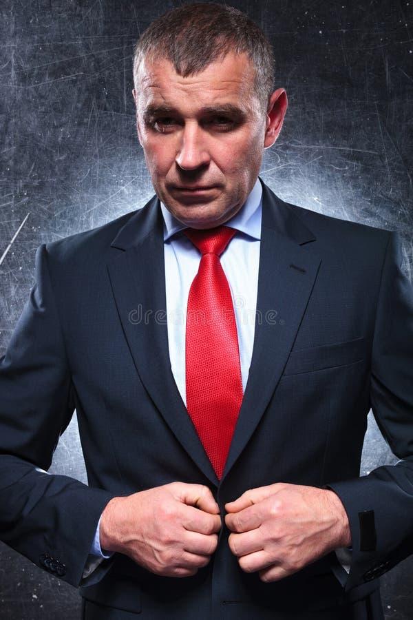Vieil homme beau d'affaires boutonnant son costume photo libre de droits
