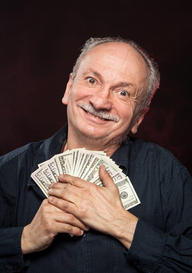 Vieil homme chanceux avec des billets d'un dollar photographie stock