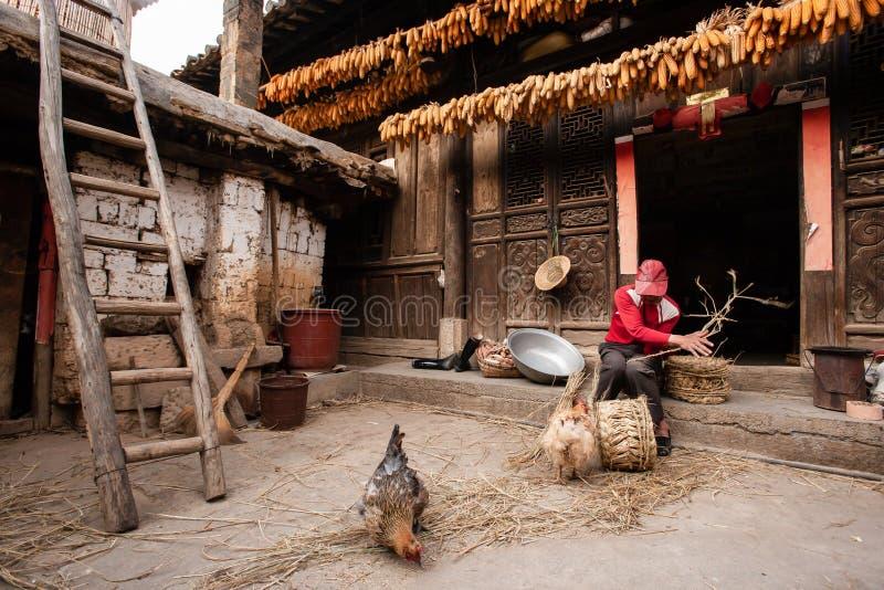 Vieil homme chinois faisant une chaise de maïs devant la vieille maison chinoise avec du charme, texture en bois de bel art, séch photographie stock libre de droits