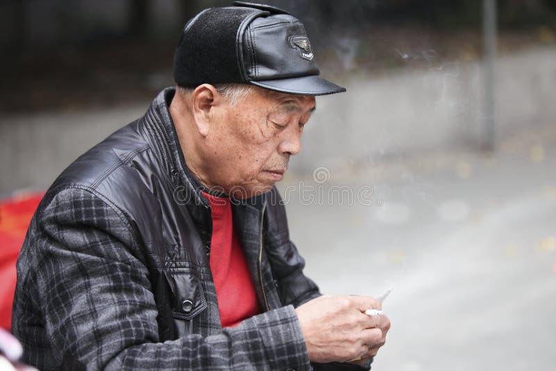 Vieil homme chinois fumant et jouant à Hangzhou, Chine photo libre de droits