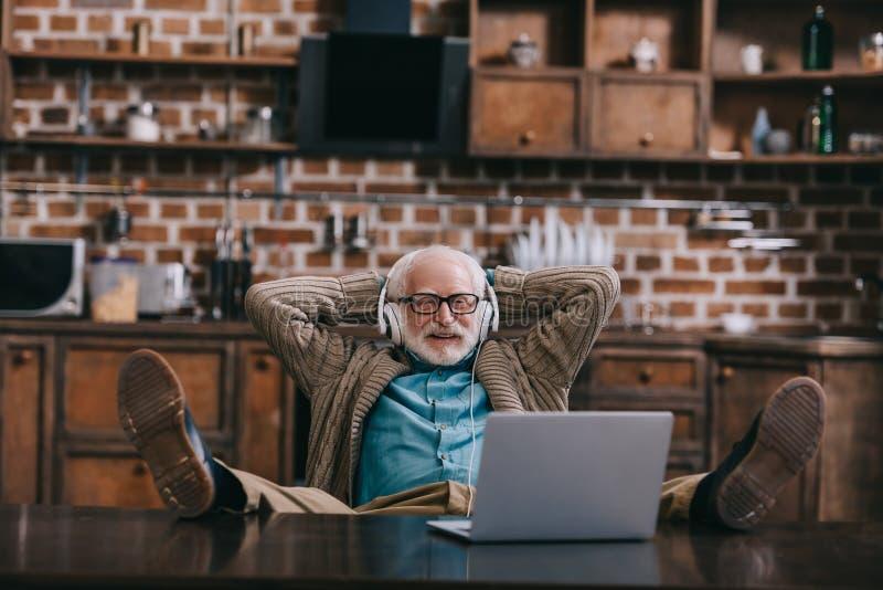 Vieil homme décontracté dans des écouteurs utilisant l'ordinateur portable avec des pieds photographie stock libre de droits