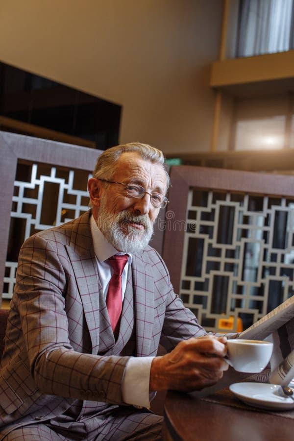 Vieil homme d'affaires avec l'ordinateur portable à la pause-café dans son concept de bureau photo stock