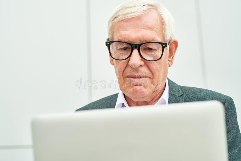 Vieil homme d'affaires avec l'ordinateur portatif photographie stock libre de droits
