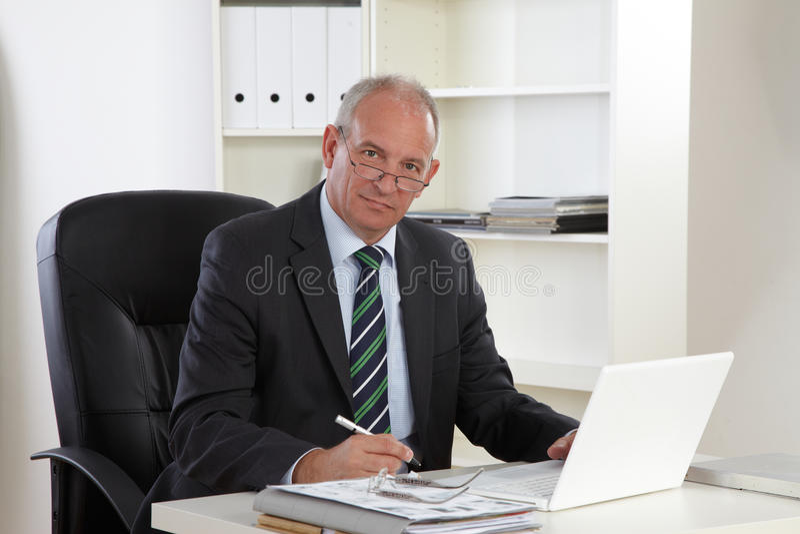 Vieil homme d'affaires avec l'ordinateur portatif image stock