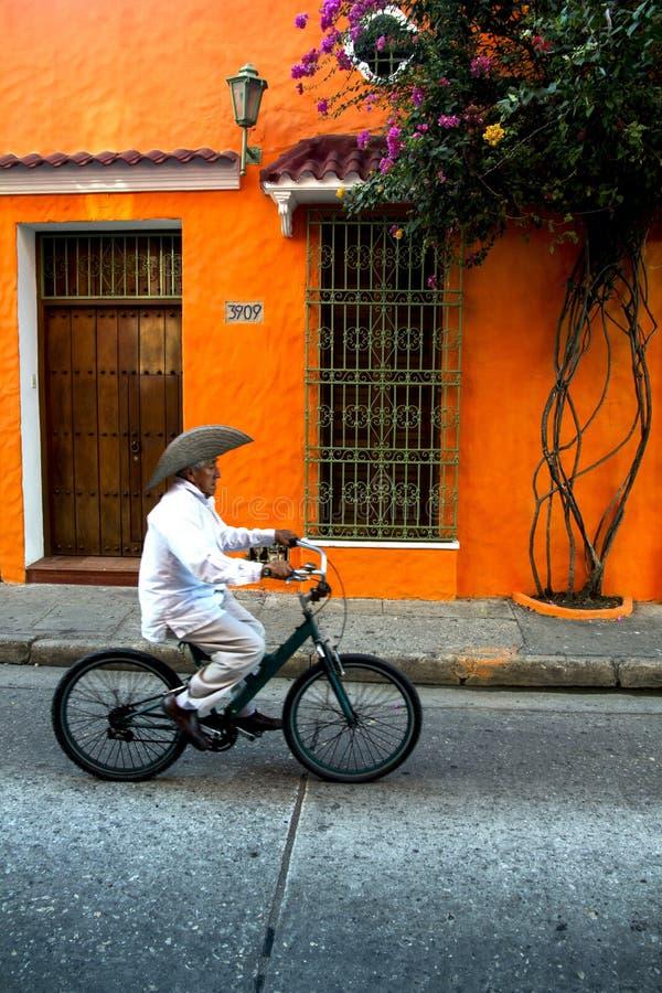 Vieil homme dans le chapeau de cowboy faisant un cycle le long de la maison orange colorée de passé de rue tranquille photographie stock
