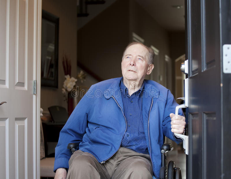 Vieil homme dans le fauteuil roulant à l'entrée principale images libres de droits