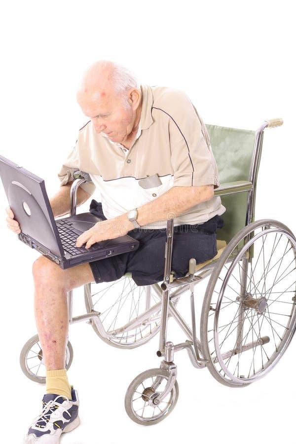 Vieil homme dans le fauteuil roulant sur la verticale d'ordinateur portatif photo libre de droits