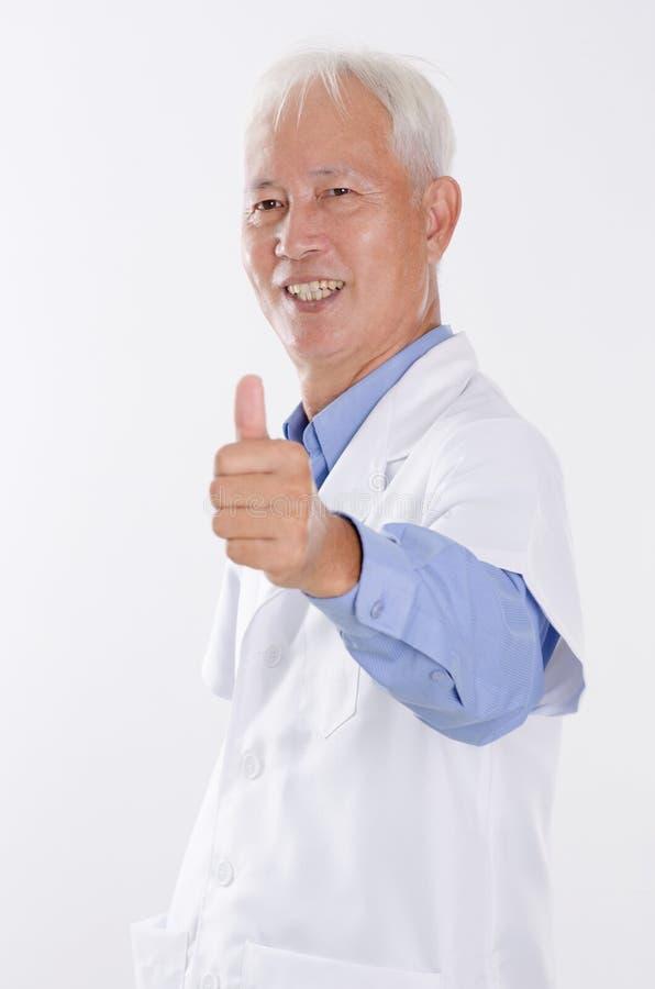Vieil homme dans le manteau de laboratoire renonçant au pouce images libres de droits