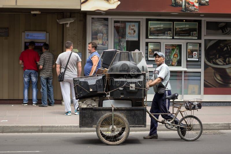 Vieil homme de la communauté de Roma vieux et obsolètes téléviseurs de achat de cathode de tube, et d'autres appareils électroniq photos libres de droits