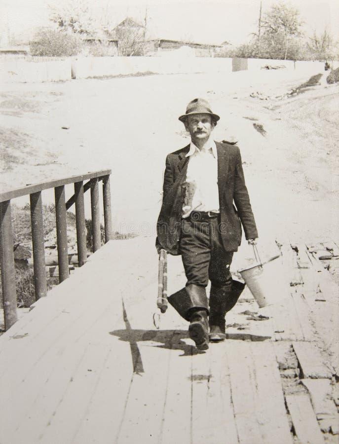 Vieil homme de photo de vintage avec une canne à pêche photo stock