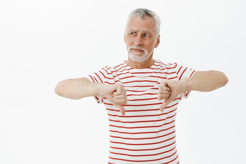Vieil homme donnant le retour négatif pour le placer a visité Portrait d'homme barbu supérieur bel contrarié et détaché photos libres de droits