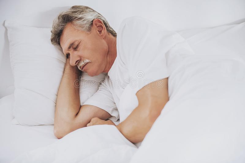 Vieil homme dormant dans le lit blanc confortable à la maison images stock