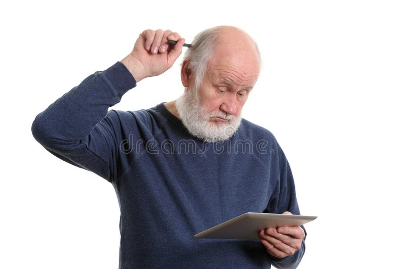 Vieil homme drôle utilisant la tablette et perplexe, d'isolement sur le blanc photographie stock