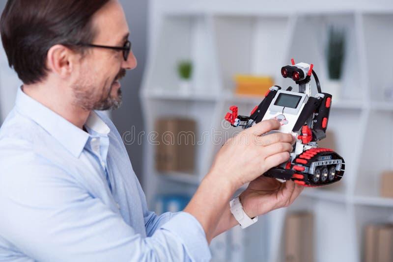 Vieil homme enthousiaste essayant le travail de peu de droid photographie stock