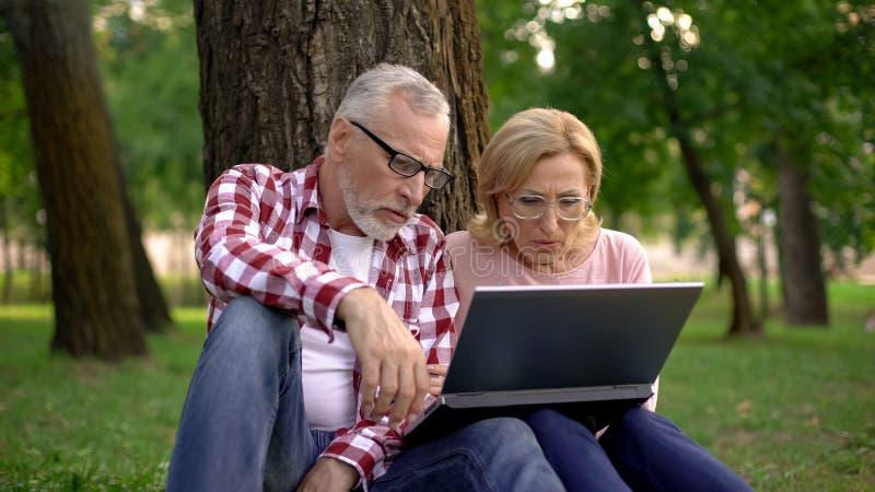 Vieil homme et femme s'asseyant sur l'herbe et la remorque de observation de film de thriller sur l'ordinateur portable image stock