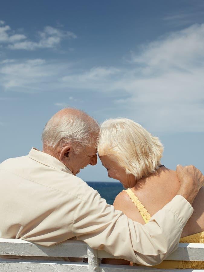 Vieil homme et femme sur le banc à la mer images stock