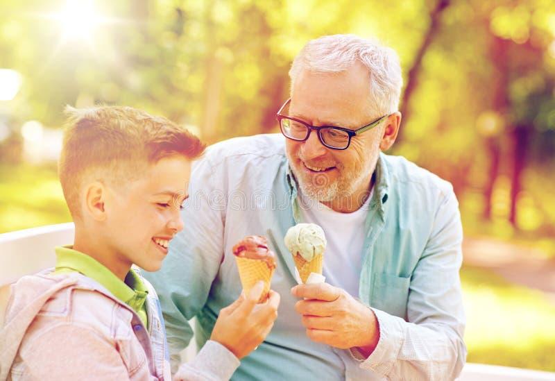 Vieil homme et garçon mangeant la crème glacée au parc d'été photographie stock libre de droits