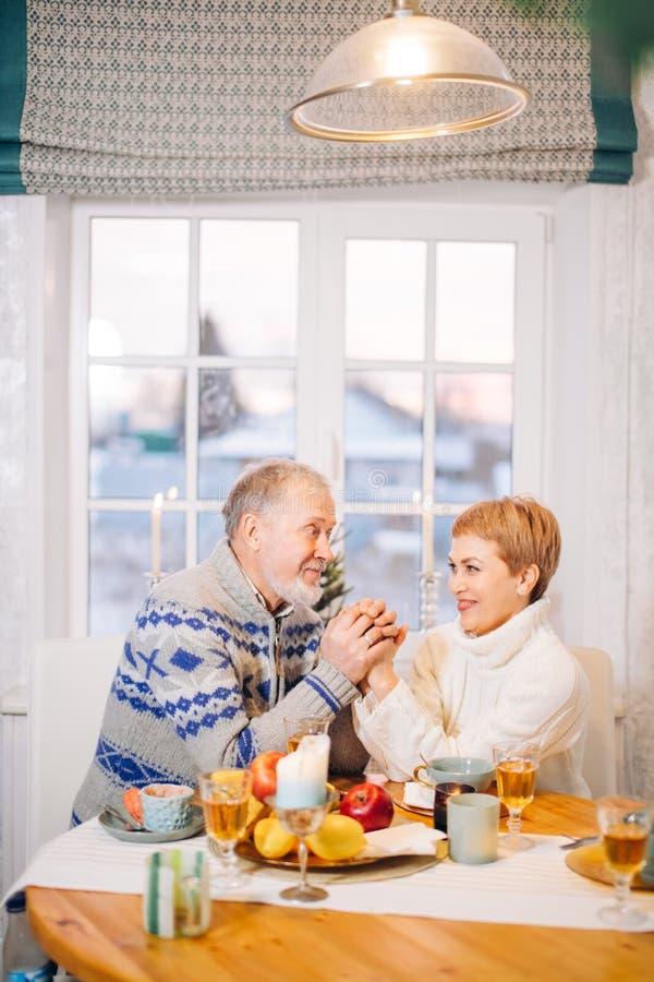 Vieil homme heureux et belle jeune femme tenant les mains de chacun photos stock