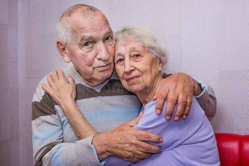 Vieil homme heureux et femme mûrs affectueux embrassant regardant la caméra image libre de droits