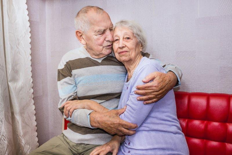 Vieil homme heureux et femme mûrs affectueux embrassant regardant la caméra images stock