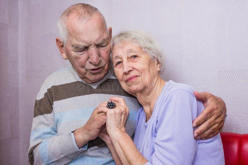 Vieil homme heureux et femme mûrs affectueux embrassant regardant la caméra photographie stock