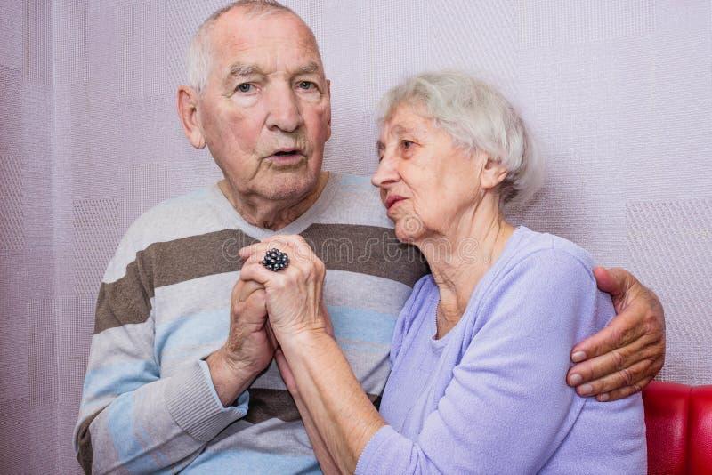 Vieil homme heureux et femme mûrs affectueux embrassant regardant la caméra photo stock