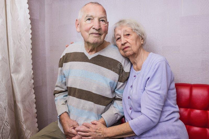Vieil homme heureux et femme mûrs affectueux embrassant regardant la caméra image stock