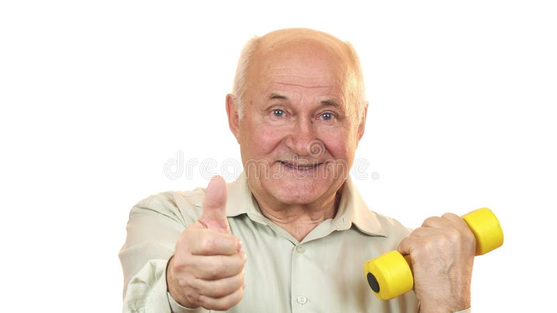 Vieil homme heureux montrant des pouces établissant avec une haltère photos stock