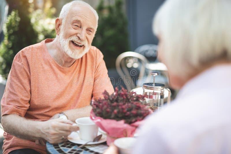 Vieil homme heureux parlant à l'épouse dehors photos stock