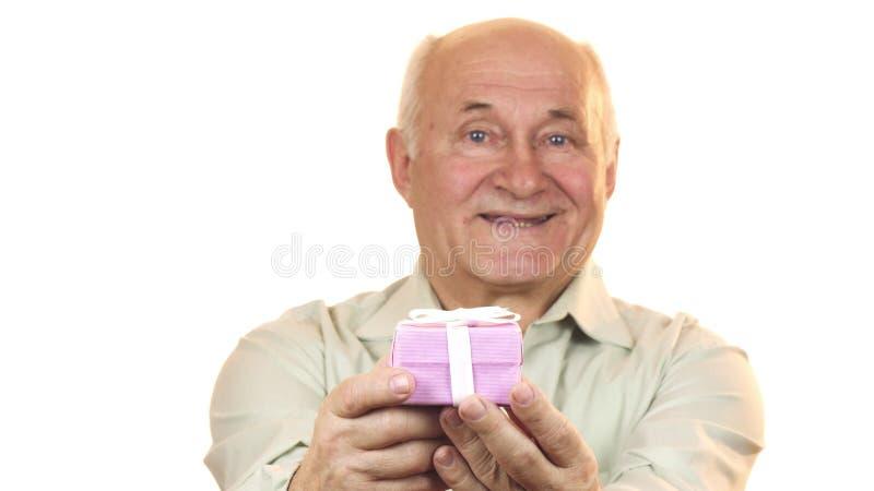 Vieil homme heureux souriant joyeux donnant un boîte-cadeau sur l'appareil-photo photos stock