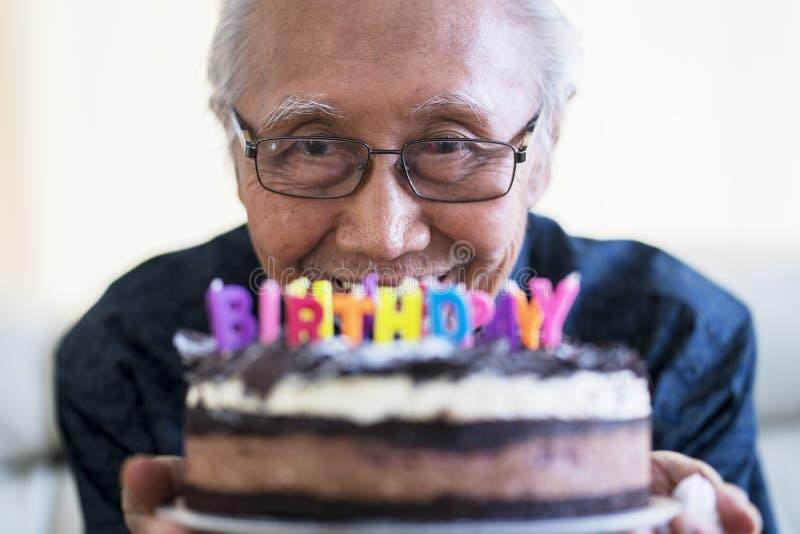 Vieil homme heureux tenant le gâteau d'anniversaire de chocolat images libres de droits