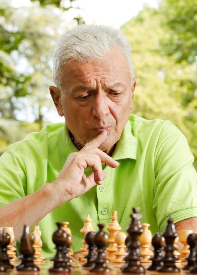 Vieil homme inquiété jouant aux échecs à l'extérieur photographie stock