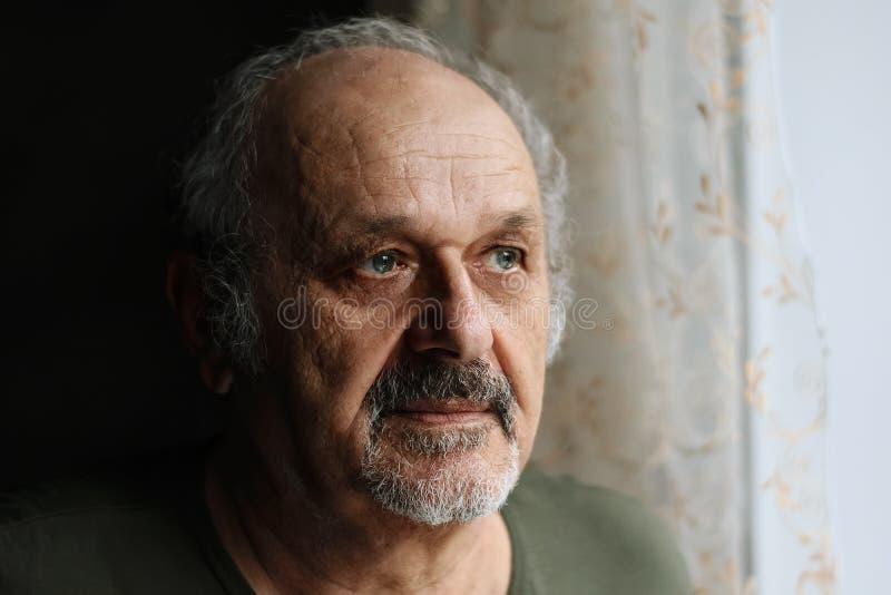 Vieil homme malheureux à l'intérieur : homme supérieur avec la position grise de barbe et de moustache près de la fenêtre Solitud photos stock