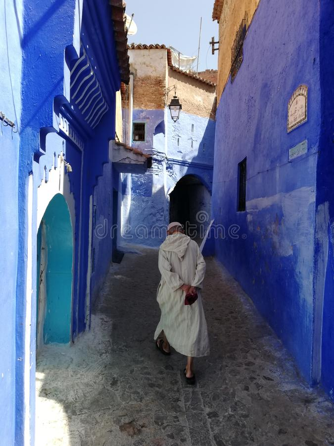 Vieil homme marchant dans Chefchaouen Médina image libre de droits