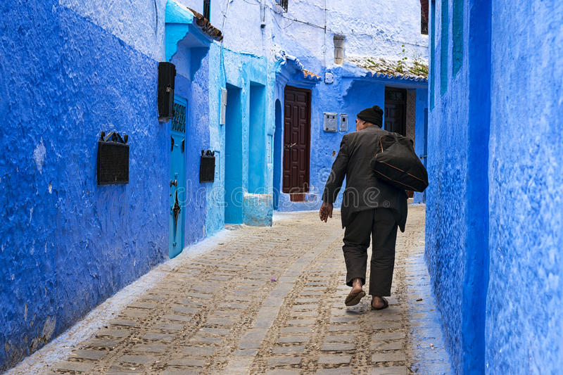Vieil homme marchant dans une rue de la ville de Chefchaouen au Maroc photo stock