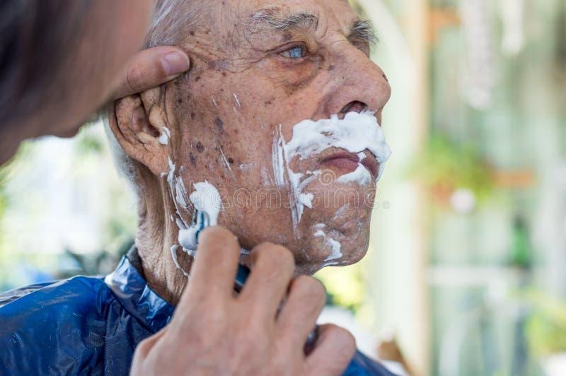 Vieil homme obtenant sa barbe rasée par le jeune homme qualifié à la maison image libre de droits