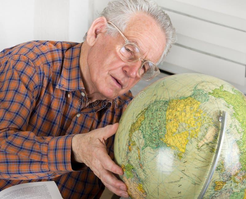 Vieil homme regardant le globe photos libres de droits