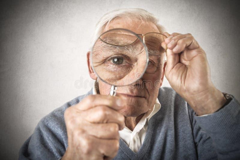 Vieil homme regardant par une lentille de main images stock