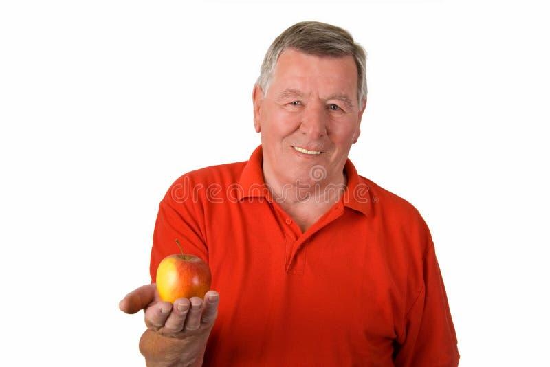 Vieil homme retenant une pomme photo stock