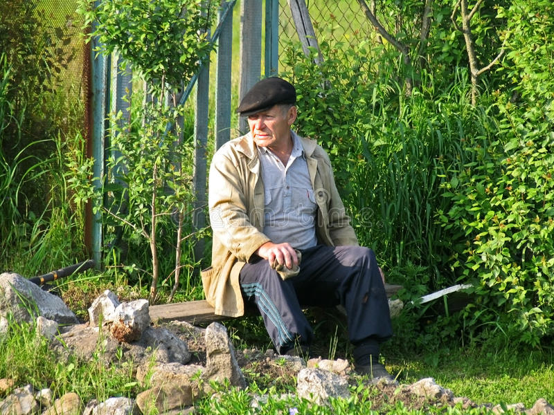Vieil homme rural se reposant sur un banc images stock
