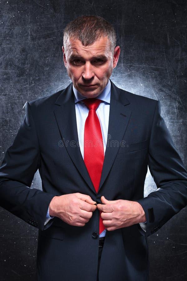 Vieil homme sérieux d'affaires déboutonnant son costume photographie stock libre de droits