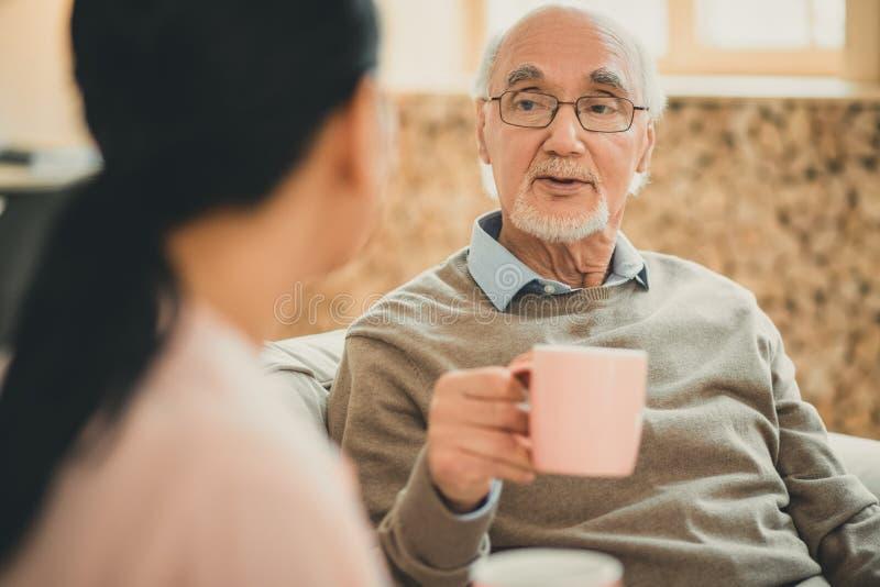 Vieil homme sage avec la tasse rose parlant à la dame châtain photographie stock