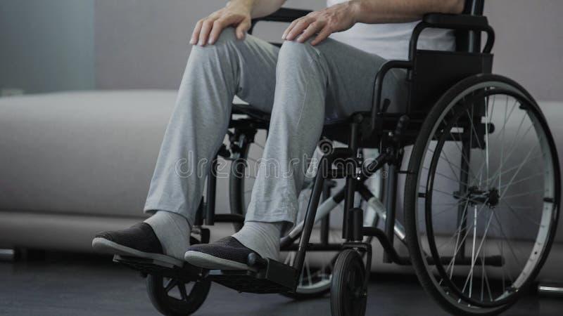 Vieil homme seul douleureux s'asseyant dans le fauteuil roulant et pensant à la vie, santé photographie stock