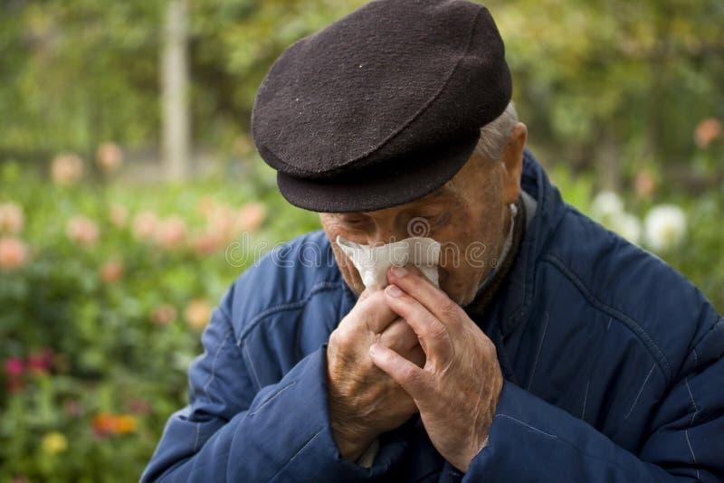 Vieil homme soufflant son nez image stock